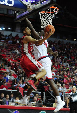 UNLV guard Jalen Poyser (24) goes up for a shot against Fresno State center Terrell Carter II (34) and forward Cullen Russo in the second half of their Mountain West Conference semifinal basketbal ...