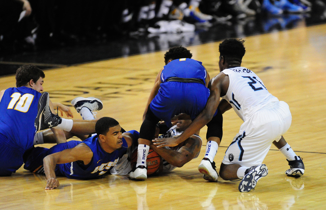 Old Dominion guard Jordan Baker, center of pile, fights UCSB guard Gabe Vincent, left, on floor, and guard Eric Childress for a loose ball in the second half of their NCAA college basketball game  ...