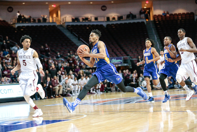 California State University, Bakersfield forward Jaylin Airington (11) stretches out on the way to the basket, while being paced by New Mexico State guard Matt Taylor (5) during the Western Athlet ...