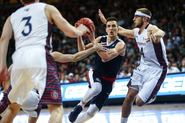 Gonzaga guard Kyle Dranginis (3) drives toward the net past Saint Mary's forward Calvin Hermanson (24) during the West Coast Conference basketball championship game at the Orleans Arena in Las Veg ...