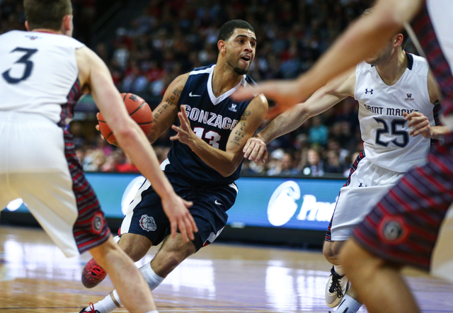 Gonzaga guard Eric McClellan (23) drives toward the net against Saint Mary's guards Joe Rahon (25) and Emmett Naar (3) during the West Coast Conference basketball championship game at the Orleans  ...