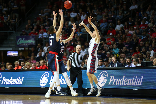 Saint Mary's guard Joe Rahon (25) makes a pass over Gonzaga forward Kyle Wiltjer (33) and Gonzaga guard Kyle Dranginis (3) during the West Coast Conference basketball championship game at the Orle ...