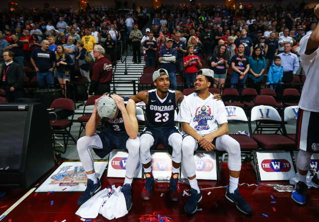 Gonzaga guards Kyle Dranginis (3), Eric McClellan (23) and Silas Melson (0) celebrate their 85-75 win over Saint Mary's in the West Coast Conference basketball championship game at the Orleans Are ...