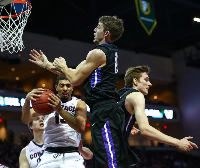 Gonzaga guard Josh Perkins (13) gets a rebound over Portland guard Jason Todd, center, during the West Coast Conference basketball tournament quarterfinals at the Orleans Arena in Las Vegas on Sat ...