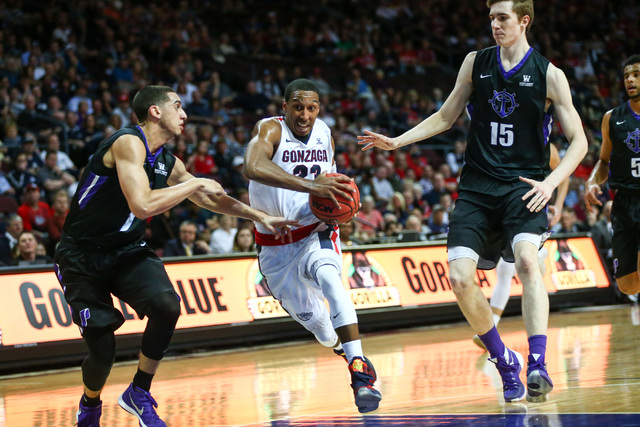 Gonzaga guard Eric McClellan (23) drives between Portland guard Bryce Pressley (1) and Portland center Philipp Hartwich (15) during the West Coast Conference basketball tournament quarterfinals at ...