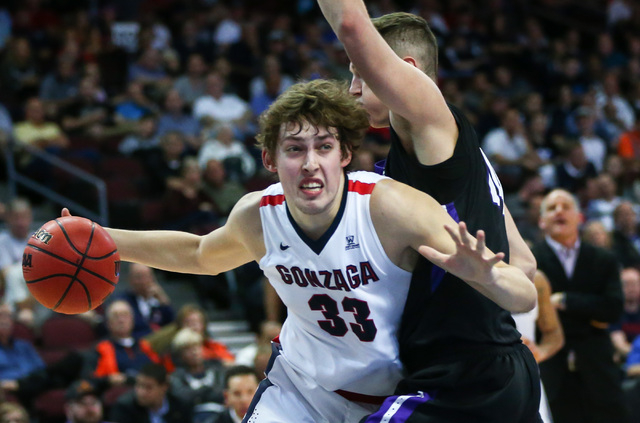 Gonzaga forward Kyle Wiltjer (33) drives past Portland forward Gabe Taylor (24) during the West Coast Conference basketball tournament quarterfinals at the Orleans Arena in Las Vegas on Saturday,  ...