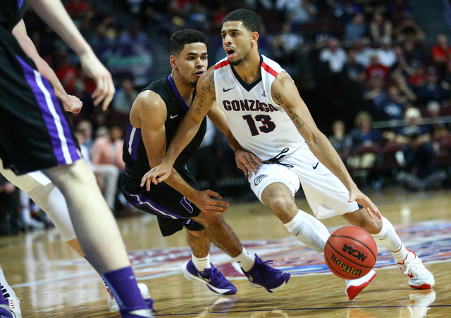 Gonzaga guard Josh Perkins (13) drives against Portland guard Alec Wintering (2) during the West Coast Conference basketball tournament quarterfinals at the Orleans Arena in Las Vegas on Saturday, ...