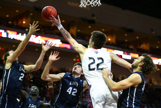 Saint Mary's forward Dane Pineau (22) reaches for a rebound as Loyola Marymount forwards Joshua Spiers (2) and Marin Mornar (42) look on during the West Coast Conference basketball tournament quar ...