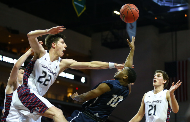 Loyola Marymount guard Brandon Brown (10) sends up a shot as Saint Mary's forward Dane Pineau (22) and Saint Mary's center Evan Fitzner (21) defend during the West Coast Conference basketball tour ...