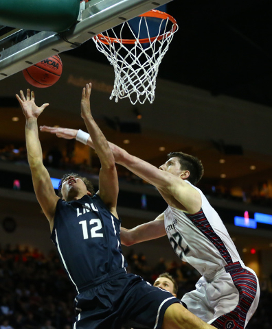 Loyola Marymount forward Steven Haney (12) attempts a shot over Saint Mary's forward Dane Pineau (22) during the West Coast Conference basketball tournament quarterfinals at the Orleans Arena in L ...