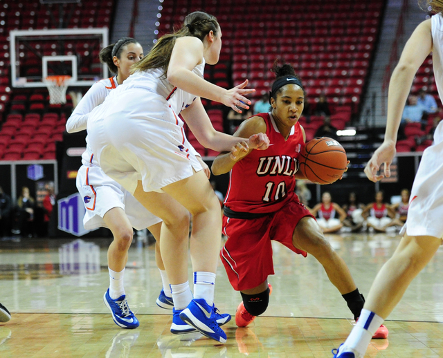 UNLV Rebels guard Nikki Wheatley (10) slips past Boise State center Miquelle Askew in the first quarter of their Mountain West Conference quarterfinal basketball game at the Thomas & Mack Cent ...