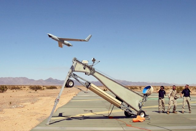 Marine Corps Sgt. Michael Kropiewnicki launches a Boeing ScanEagle drone during the 2006 training exercise Desert Talon at the Marine Corps Air Station Yuma, Ariz. Flight tests for a developmental ...
