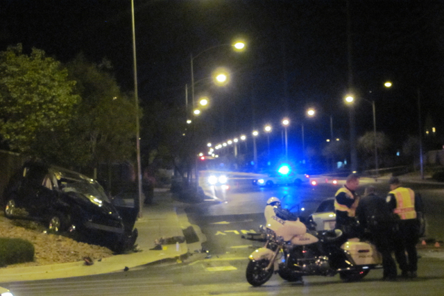 One car sits off the road and another remains in the eastbound lane of Tropical Avenue (behind police motorcycle) at North 5th Street in after a crash killed one person and injured six others in N ...