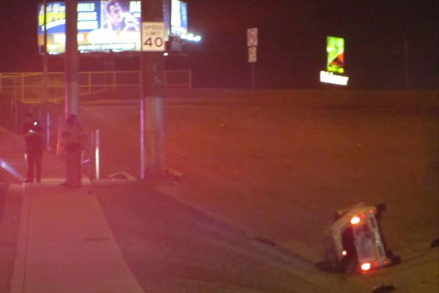 A car rests on its side off the westbound lanes of Cheyenne Avenue just before it crosses I-15 in Las Vegas on Wednesday, March 9, 2016. Cheyenne is closed in both directions while police investig ...