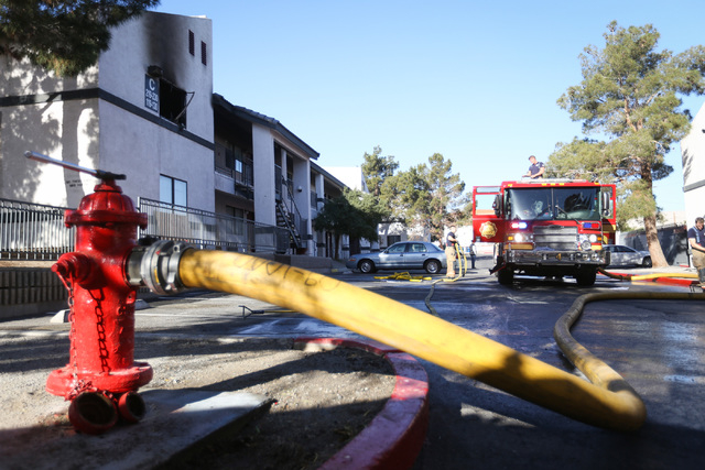 Firefighters pack up equipment after putting out a fire at Hidden Village Apartments near the intersection of Fremont Street and Charleston Boulevard on Thursday, March 17, 2016. Brett Le Blanc/La ...