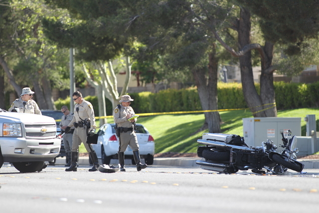 Las Vegas police officers investigate the scene of a crash involving a Metro motorcycle officer on Durango Drive south of Starboard Avenue in Las Vegas on Friday, March 25, 2016. (Brett Le Blanc/L ...