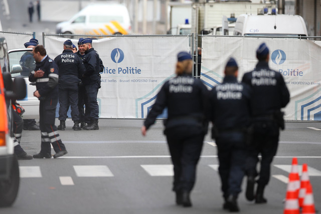 Police stand near a perimeter fence in Brussels following a bomb attack on Maelbeek metro station on Tuesday, March 22, 2016.  (Bloomberg photo by Jasper Juinen)