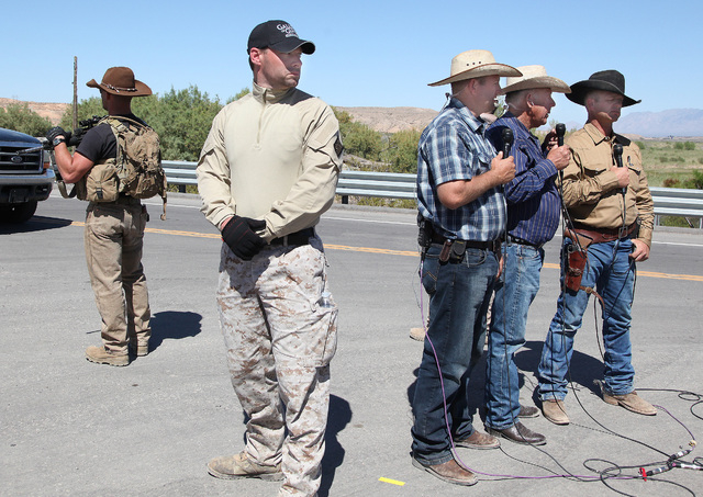 Armed guards surround Ammon Bundy, Cliven Bundy and Ryan Bundy as they do a remote interview with Sean Hannity of Fox News near Cliven Bundy's ranch in Bunkerville on Monday, April 14, 2014. (Just ...