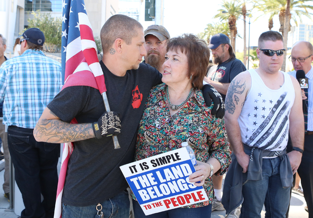 Brian Enright, left, hugs Carol Bundy, wife of Cliven Bundy, as she arrives to protest outside Lloyd George Federal Building on Thursday, March 10, 2016, in Las Vegas. Cliven Bundy appears in cour ...