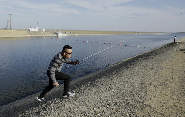 Sha Xinog climbs the bank to get more bait while fishing along the California Aquaduct near Firebaugh, Calif., on Feb. 25, 2016. (AP Photo/Rich Pedroncelli)