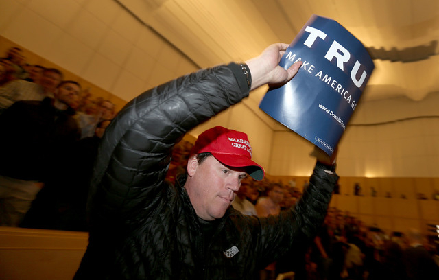 A Donald Trump supporter exits the auditorium after listening to Mitt Romney's speech on the Republican presidential at the University of Utah, Thursday, March 3, 2016, in Salt Lake City. (Laura S ...