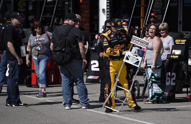 NASCAR Xfinity Series driver Brandon Gaughan accidentally knocks over a signature card holder for fellow driver Brennan Poole before the start of the second practice session for the Boyd Gaming 30 ...