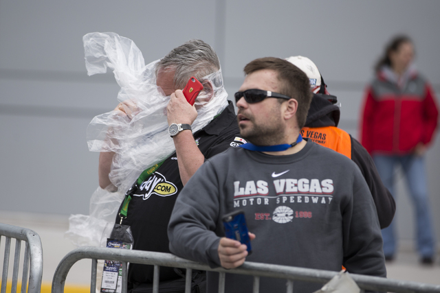 A man struggles with the wind before the NASCAR Sprint Cup Series Kobalt 400 race at the Las Vegas Motor Speedway in Las Vegas on Sunday, March 6, 2016, in Las Vegas. Erik Verduzco/Las Vegas Revie ...