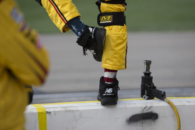 A crew member for Joey Logano (22) stands on a safety barrier during the NASCAR Sprint Cup Series Kobalt 400 race at the Las Vegas Motor Speedway in Las Vegas on Sunday, March 6, 2016, in Las Vega ...