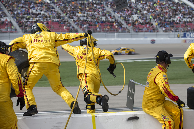 Crew members leap over a safety barrier during a pit stop by Joey Logano (22) in the NASCAR Sprint Cup Series Kobalt 400 race at the Las Vegas Motor Speedway in Las Vegas on Sunday, March 6, 2016, ...