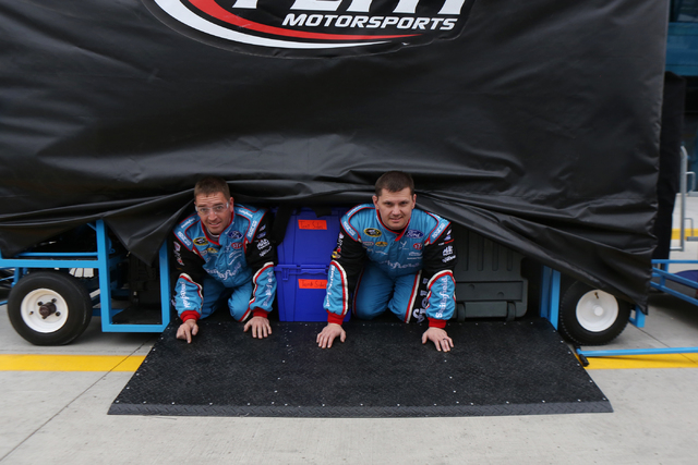 Crew members take cover during a passing storm before the NASCAR Sprint Cup Series Kobalt 400 race at the Las Vegas Motor Speedway in Las Vegas on Sunday, March 6, 2016, in Las Vegas. Erik Verduzc ...