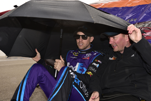 Denny Hamlin waits out a rain delay with a crew member before the start of the Kobalt 400 at Las Vegas Motor Speedway in Las Vegas Sunday, March 6, 2016. Josh Holmberg/Las Vegas Review-Journal