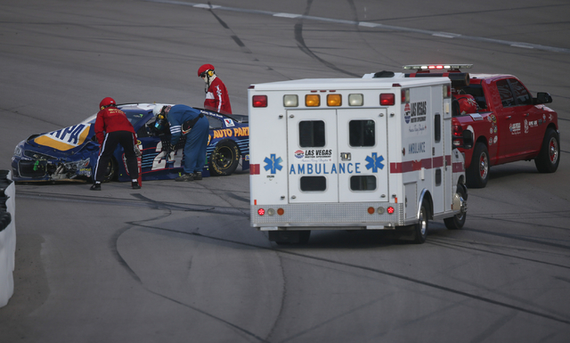Emergency officials attend to Chase Elliott (24) following a crash during the NASCAR Sprint Cup Series Kobalt 400 race at the Las Vegas Motor Speedway in Las Vegas on Sunday, March 6, 2016. Chase  ...