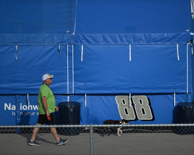 A man walks a dog in front of a Dale Earnhardt Jr (88) during Sprint Cup testing on Thursday, Mar. 3, 2016 at Las Vegas Motor Speedway. Brett Le Blanc/Las Vegas Review-Journal Follow @bleblancphoto