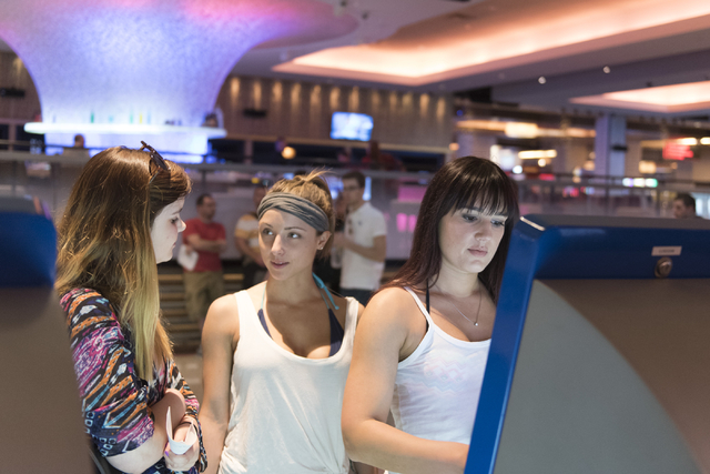 Emily Powell, right, uses one of the seven new self check-in kiosks located in the lobby at The Linq Hotel in Las Vegas Wednesday, March 16, 2016. Sarah Smith, left, and Victoria Schuler stand bes ...