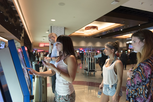 Emily Powell, left, uses one of the seven new self check-in kiosks located in the lobby at The Linq Hotel in Las Vegas Wednesday, March 16, 2016. Victoria Schuler, center, and Sarah Smith stand be ...