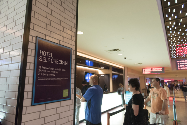 Signage for the seven new self check-in kiosks hangs on a column adjacent to the traditional check-in counter located in the lobby at The Linq Hotel in Las Vegas Wednesday, March 16, 2016. Jason O ...