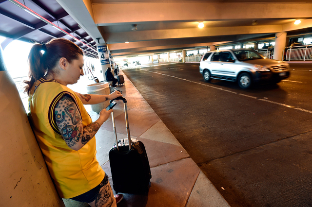 Genevieve Kocak of Las Vegas checks her cellphone as she waits for her ride in the passenger pick-up area at McCarran International Airport Monday, March 14, 2016, in Las Vegas. A cellphone lot wa ...