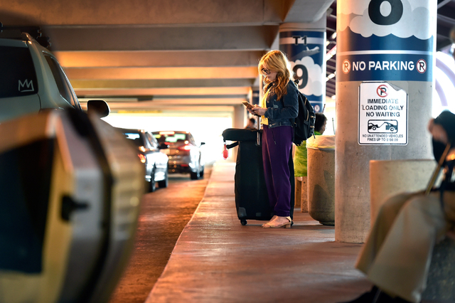 Nanette Guild of Henderson checks her cellphone as she waits for her ride in the passenger pick-up area at McCarran International Airport Monday, March 14, 2016, in Las Vegas. A cellphone lot was  ...