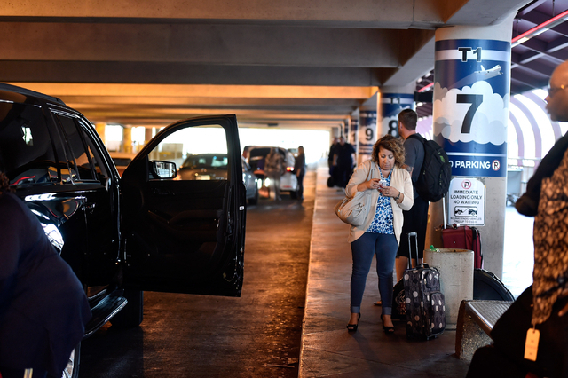 An airport passenger checks her cellphone as she waits for her ride in the passenger pick-up area at McCarran International Airport Monday, March 14, 2016, in Las Vegas. A cellphone lot was establ ...