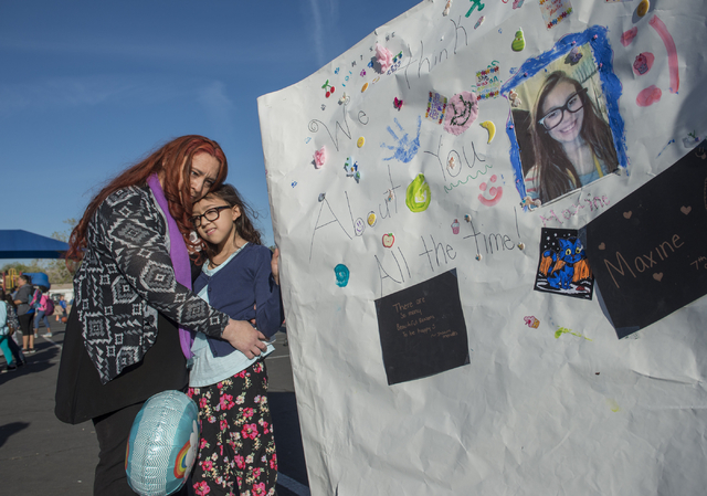 Christina Lopez hugs her daughter Jordan, 9, Wednesday, March 6, 2016, during a walk to honor her other daughter Maxine, 12, who recently died after being taken to the hospital with pain in her ne ...