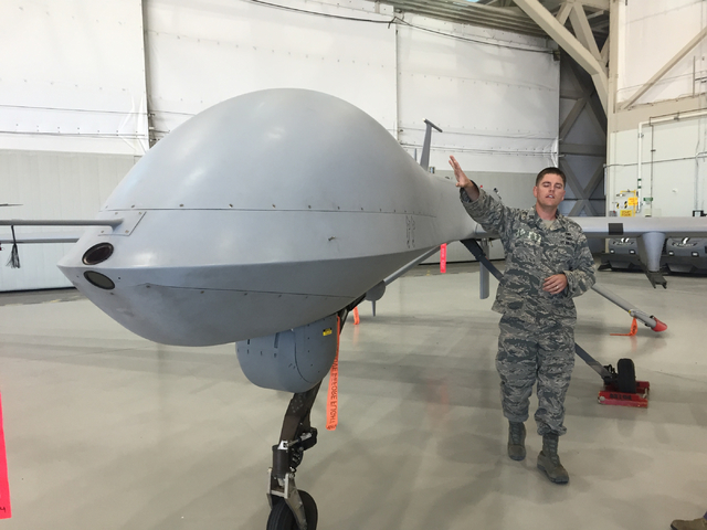 Capt. Will, a maintenance officer, pats the fuselage of an MQ-1B Predator aircraft inside a hangar June 16, 2015, at Creech Air Force Base. Certain personnel involved with remotely piloted aircraf ...