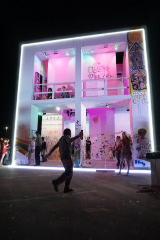 Life Cube artist Scott Cohen, center, dances as the LED lights are turned on during the illumination ceremony for the Life Cube in the Llama Lot at Fremont Street and 9th Street in Las Vegas Satur ...
