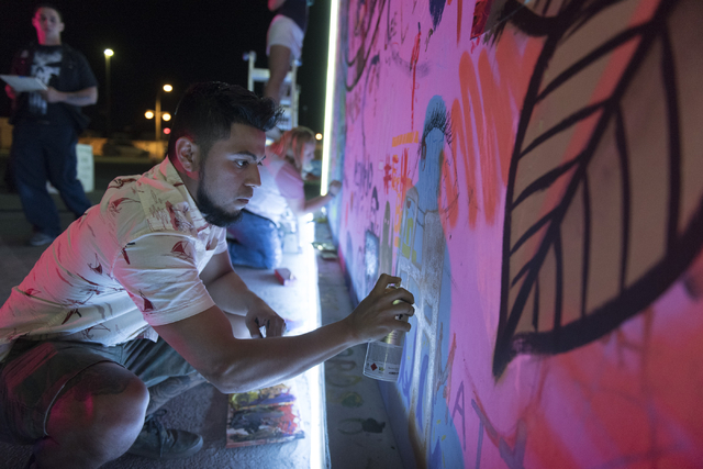 """Herminio """"Herms"""" Alvarez paints during the illumination ceremony for the Life Cube in the Llama Lot at Fremont Street and 9th Street in Las Vegas Saturday, March 19, 2016. The ce ..."""