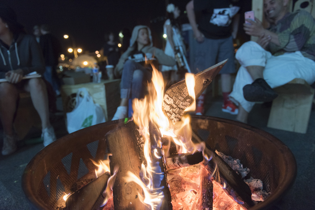 Friends hang around a bonfire during the illumination ceremony for the Life Cube in the Llama Lot at Fremont Street and 9th Street in Las Vegas Saturday, March 19, 2016. The ceremony kicks off two ...