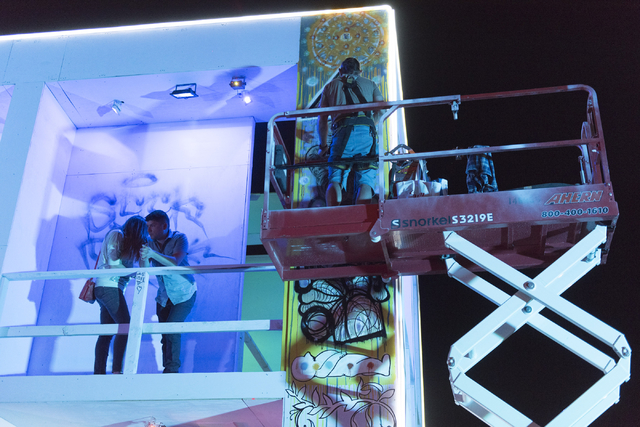 Jason Garuda, right, paints during the illumination ceremony for the Life Cube in the Llama Lot at Fremont Street and 9th Street in Las Vegas Saturday, March 19, 2016. The ceremony kicks off two w ...