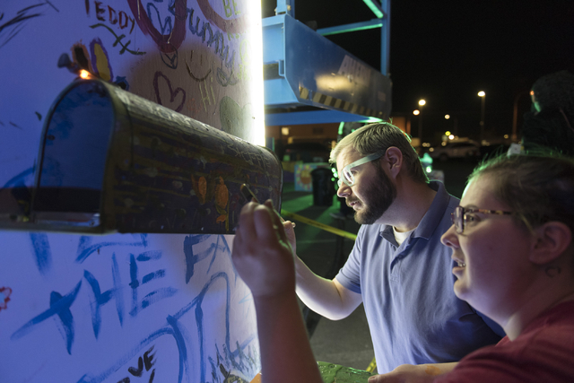 Lance Wilson, left, and Jami Velez paint during the illumination ceremony for the Life Cube in the Llama Lot at Fremont Street and 9th Street in Las Vegas Saturday, March 19, 2016. The ceremony ki ...