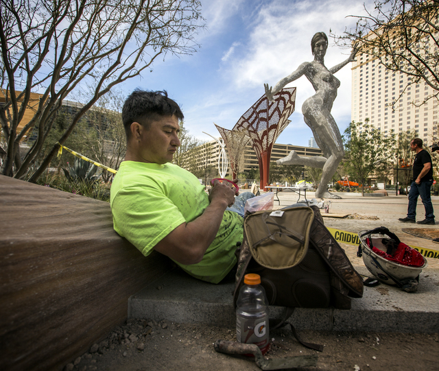 "Construction worker Steve Gonzales takes a lunch break near the ""Bliss Dance"" sculpture created by Marco Cochrane during an unveiling at The Park, MGM Resorts International's outdoor dining and en ..."