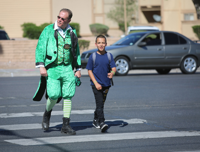 Clark County School District Officer Robert Mayer helps a child cross Tropicana Avenue at Morris Street on Thursday, March 17, 2016. Nevada Highway Patrol, Henderson Police and CCSD police teamed  ...