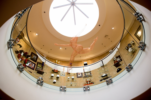 Hanging above a circular, two-story office is a fiber-optic cable sculpture of a ballerina that moves. The office's second floor is a sport memorabilia museum. (TONYA HARVEY/REAL ESTATE MILLIONS)
