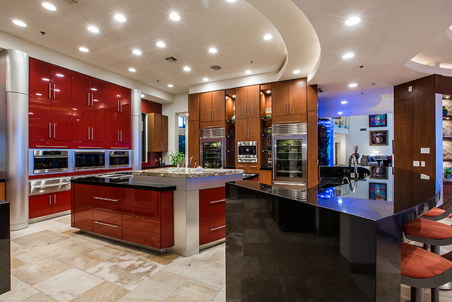 (COURTESY OF Shapiro & Sher Group)   The kitchen is dressed in deep reds and has upgraded appliances.